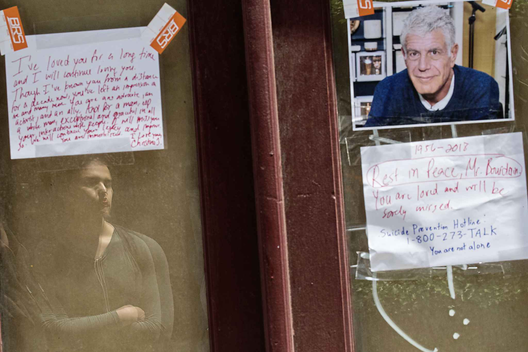 Gaela Solo, of Brooklyn, is reflected on a window as she pays her respects to Anthony Bourdain at a make shift memorial outside the building that once housed Le Halles restaurant on Park Avenue, Friday, June 8, 2018, in New York. (AP Photo/Mary Altaffer)
