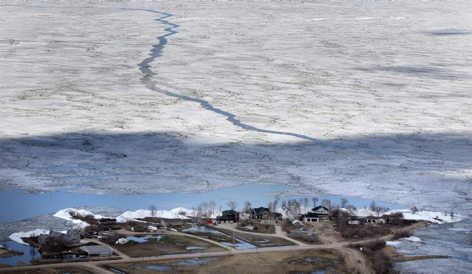 Looking out over Dauphin Lake the thawing ice still floats on the lake, and the shore where the ice shove destroyed homes can be seen in the foreground. (Phil Hossack / Winnipeg Free Press)