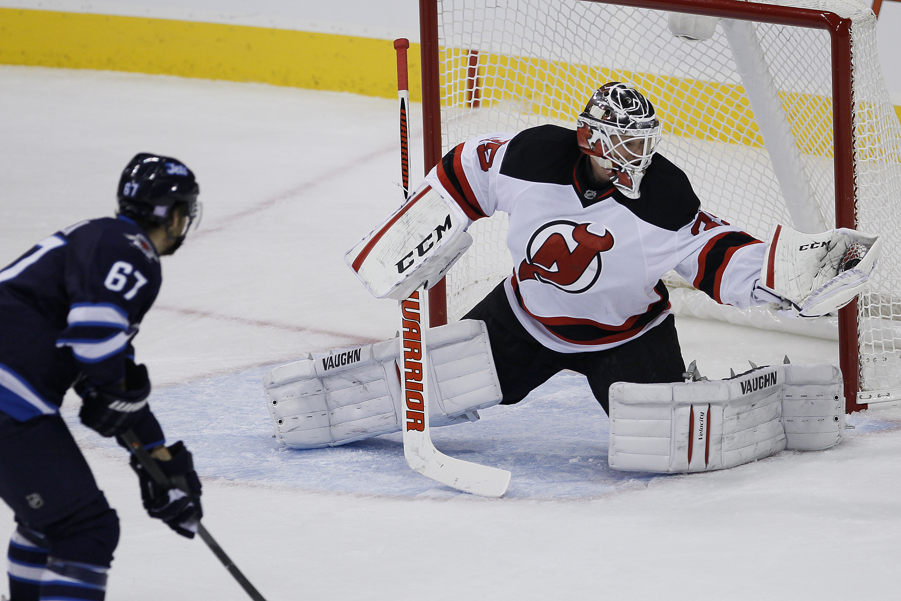 Cory Schneider gets his glove on the shot from Michael Frolik during the first period.