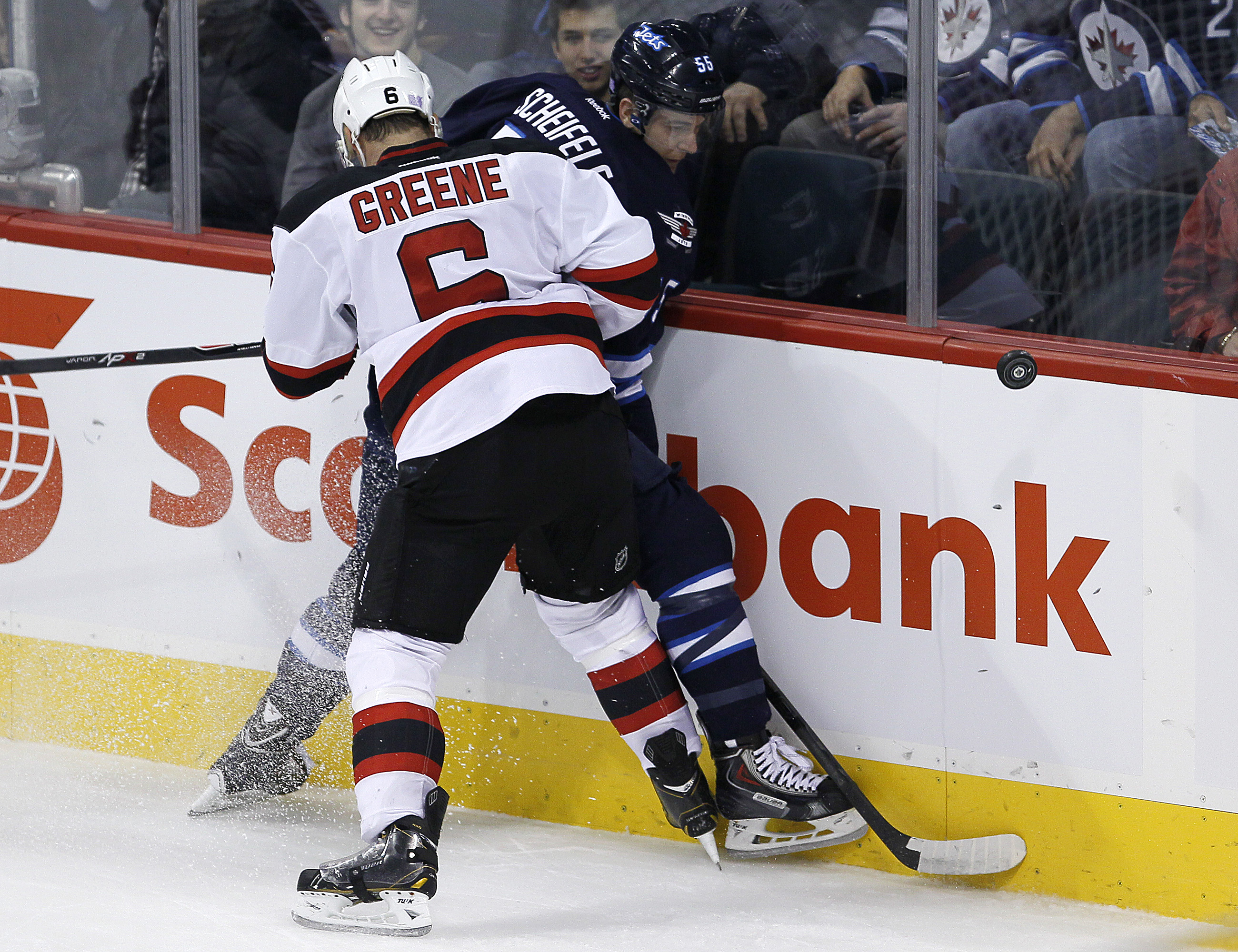 Mark Scheifele gets tied up by Andy Greene during the first period.