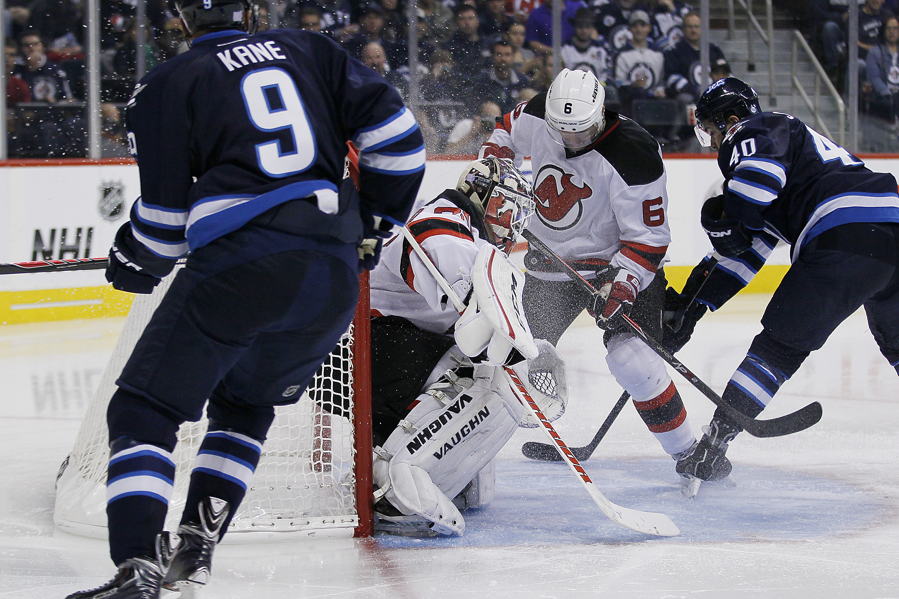 Evander Kane's shot deflects off New Jersey Devils' Andy Greene and past goaltender Cory Schneider for the Jets first goal during the second period.