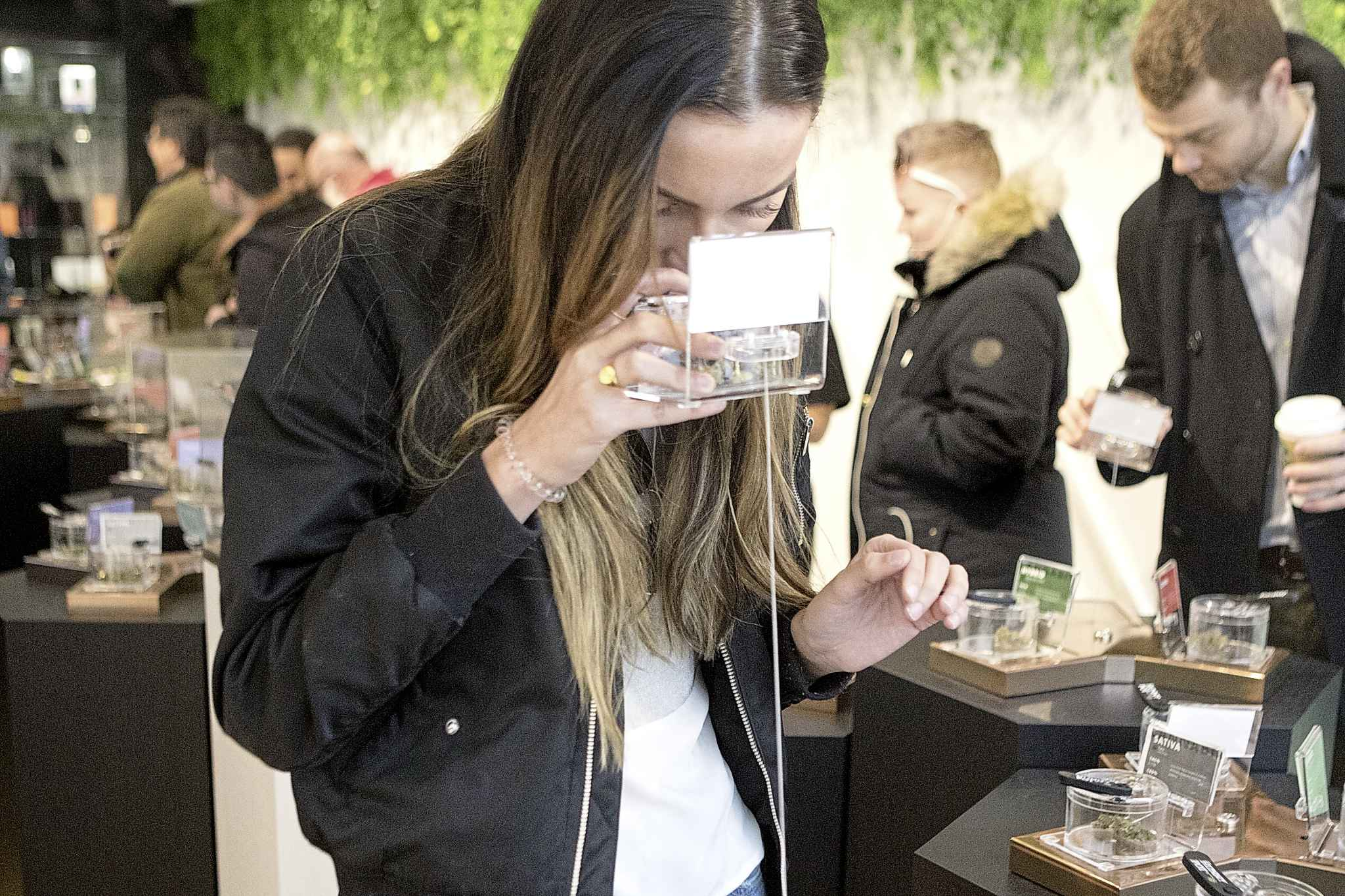A customer smells a sample as she shops for cannabis Monday on the first morning of opening for Toronto's Hunny Pot, one of the retail stores licensed to sell cannabis in Ontario. (Chris Young / The Canadian Press)