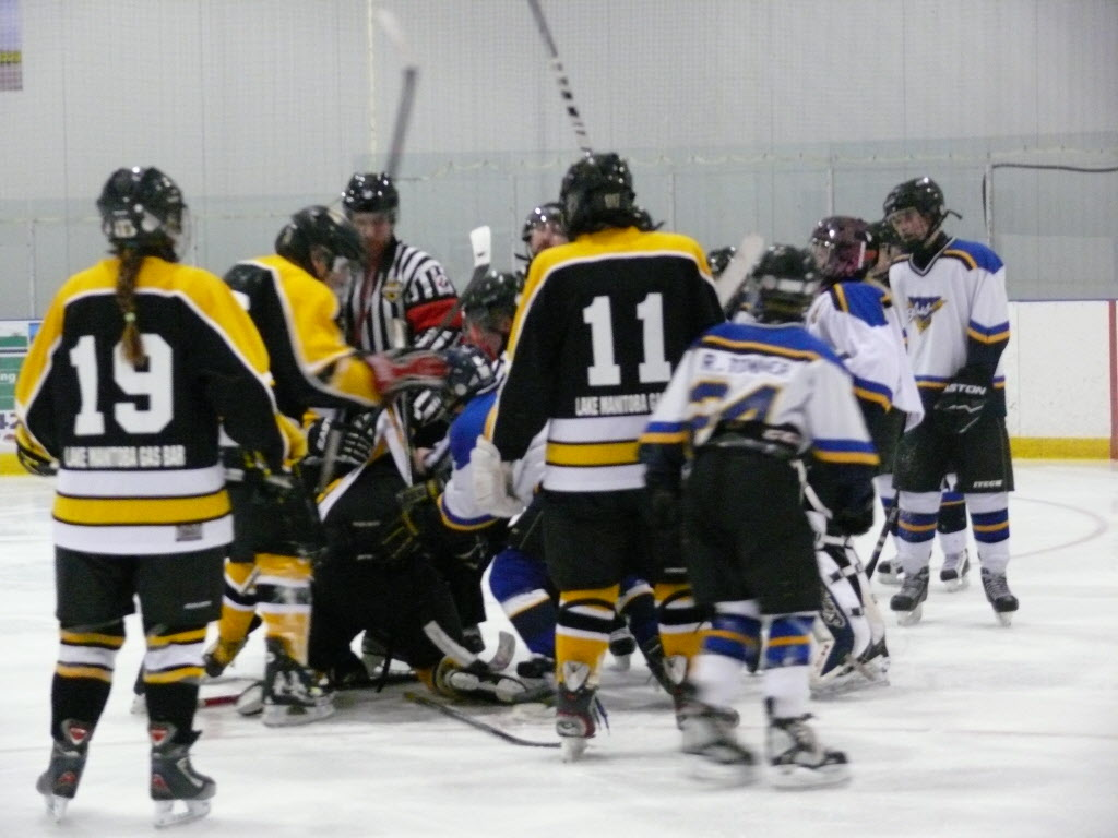 Officials intervene in the on-ice melee Sunday in which a young linesman was physically attacked.