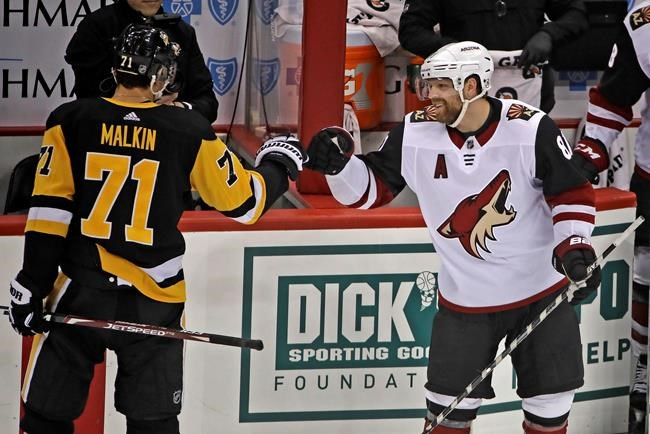 Two-time Stanley Cup Champion with the Pittsburgh Penguins, Arizona Coyotes' Phil Kessel, right, is welcomed back by former linemate Pittsburgh Penguins' Evgeni Malkin (71) following a tribute to him during a timeout in the first period of an NHL hockey game in Pittsburgh, Friday, Dec. 6, 2019. (AP Photo/Gene J. Puskar)