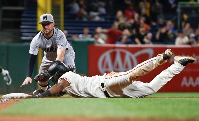 Pittsburgh Pirates' Josh Bell, right, dives in safely with a triple as Milwaukee Brewers third baseman Travis Shaw applies a late tag during the eight inning of a baseball game Friday, July 13, 2018, in Pittsburgh. The Pirates won 7-3. (AP Photo/Keith Srakocic)