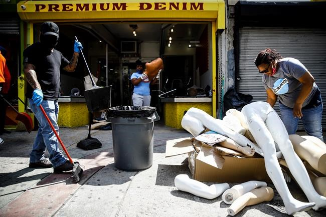 Volunteer community members clean up a looted store in Philadelphia, Monday, June 1, 2020 in the aftermath of protest and unrest in reaction to George Floyd's death while in police custody on May 25 in Minneapolis. (AP Photo/Matt Rourke)