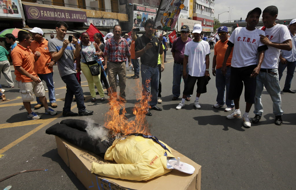 Demonstrators burn an effigy of Panamanian President Ricardo Martinelli during the annual May Day parade in Panama City on Thursday. Hundreds of Panamanians, teachers and union workers marched through the streets demanding better salaries and protested against the high cost of living.  (Arnulfo Franco / The Associated Press)