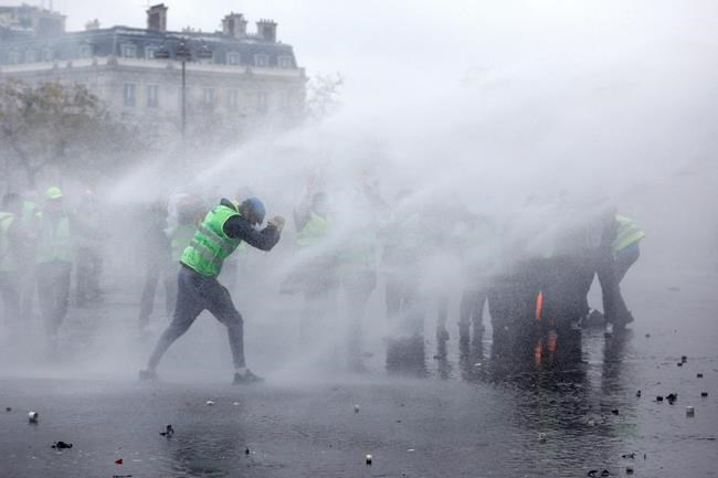 Demonstrators wearing yellow jackets face water cannons near the Champs Elysees avenue during a demonstration Saturday Dec.1 2018 in Paris. French authorities have deployed thousands of police on Paris&#39 Champs Elysees avenue to try to contain protes