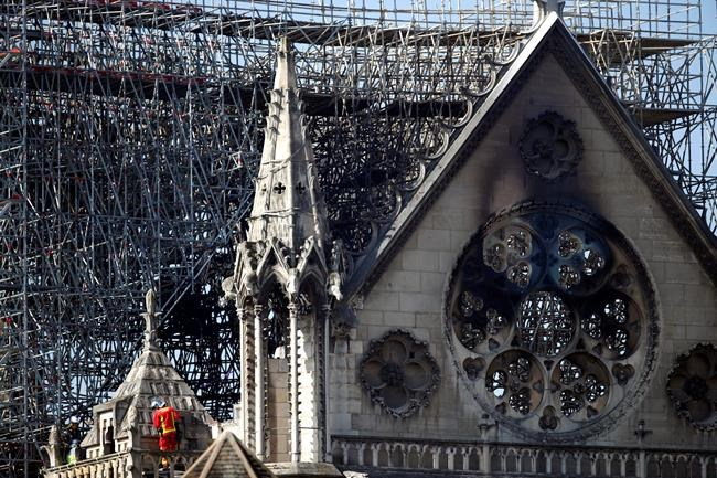 A fire fighter makes his way on a balcony of Notre Dame cathedral Wednesday, April 17, 2019 in Paris. French President Emmanuel Macron ratcheted up the pressure by setting a five-year deadline to restore the 12th-century landmark. (AP Photo/Francois Mori)