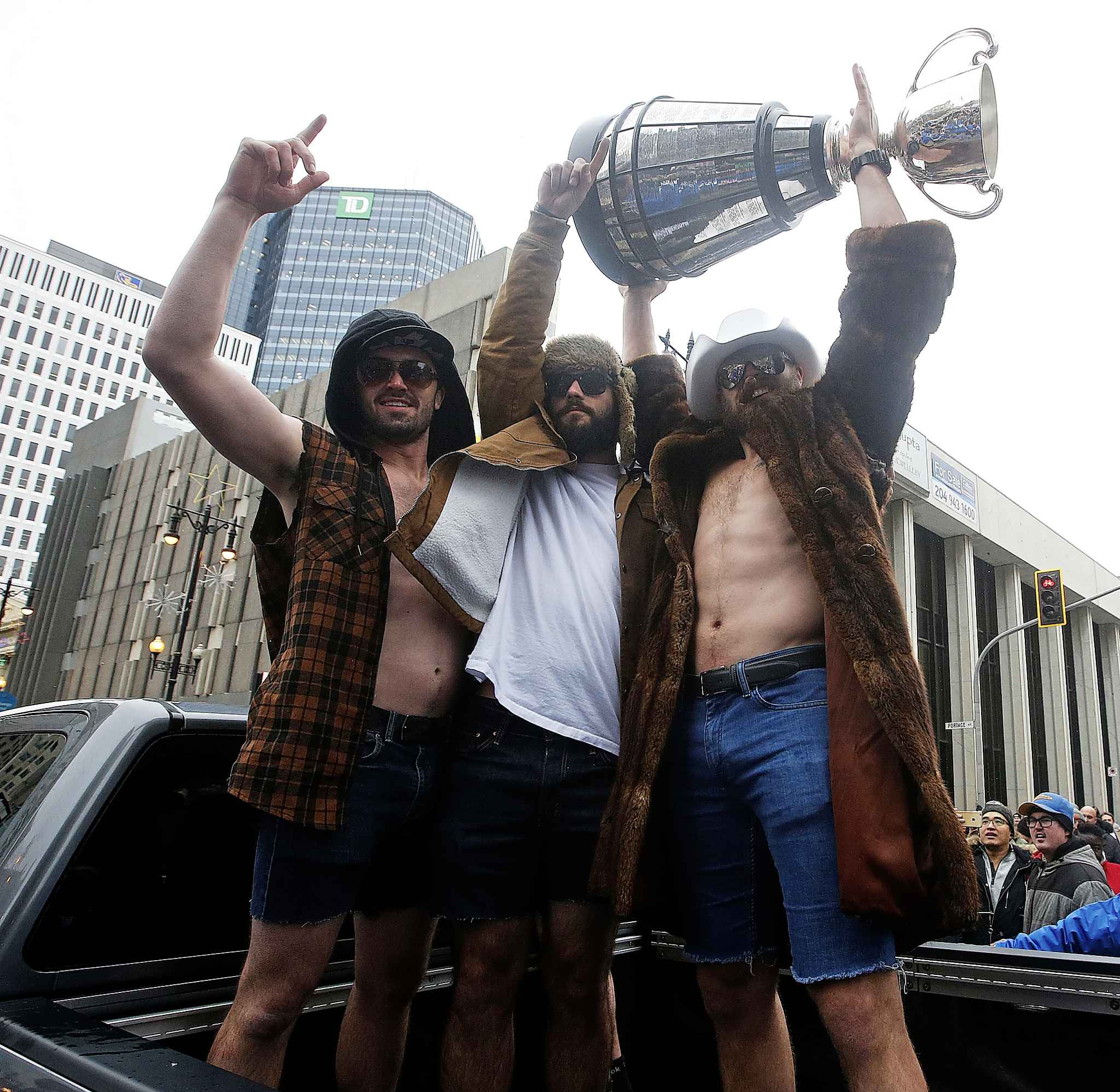 Winnipeg Blue Bombers quarterbacks, from left, Trevor Knight, Sean McGuire and Chris Streveler celebrate their Grey Cup victory with Winnipeggers during the Grey Cup parade in downtown Winnipeg, Tuesday.