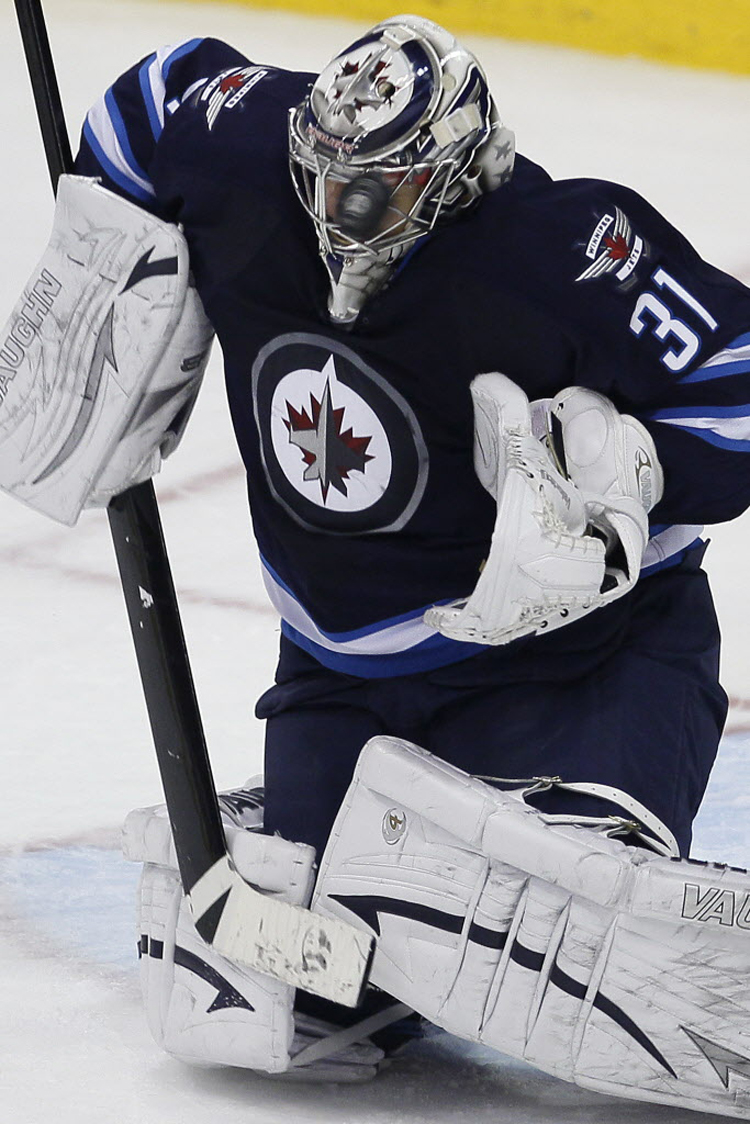A Boston Bruins' shot goes off the facemask of Ondrej Pavelec during the second period. (John Woods  / Winnipeg Free Press)