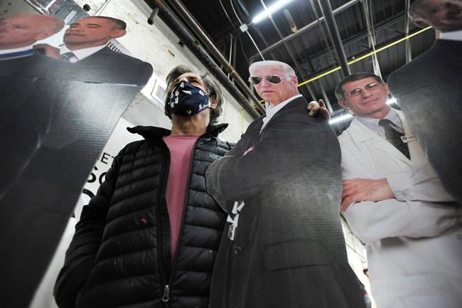 Stephen Taren, who owns Wet Paint Printing + Design in Wilkes-Barre, puts his arm around a life-sized cutout of Joe Biden with Dr. Anthony Fauci, right, and former President Obama, Tuesday Jan. 19, 2021 in Wilkes-Barre, Pa. (Mark Moran/The Citizens' Voice via AP)