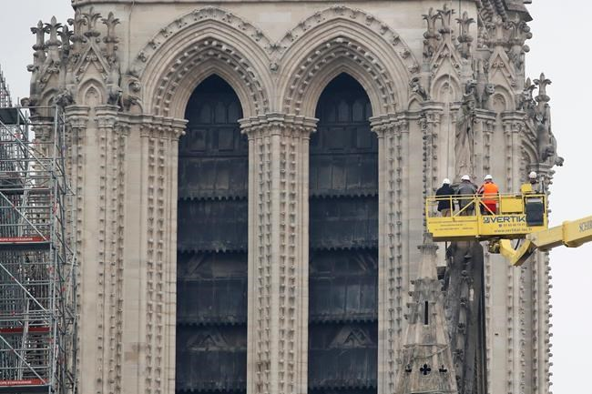 A crane lifts experts as they inspect the damaged Notre Dame cathedral after the fire in Paris, Tuesday, April 16, 2019. Experts are assessing the blackened shell of Paris' iconic Notre Dame cathedral to establish next steps to save what remains after a devastating fire destroyed much of the almost 900-year-old building. With the fire that broke out Monday evening and quickly consumed the cathedral now under control, attention is turning to ensuring the structural integrity of the remaining building. (AP Photo/Christophe Ena)