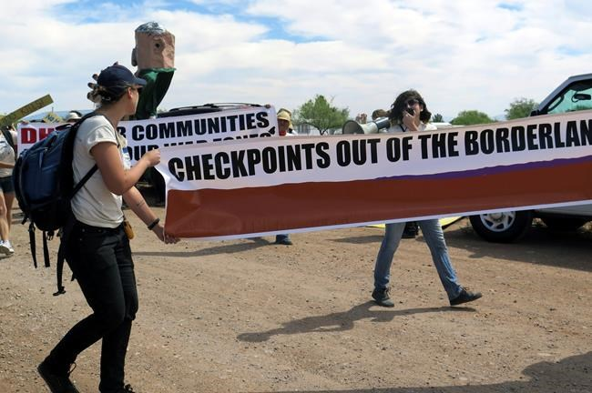FILE - In this May 27, 2015, file photo, two protesters carry a large banner as they walk toward a U.S. Border Patrol checkpoint on a two-lane road in Amado, Ariz., about 20 miles north of the Mexican border. The U.S. Circuit of Appeals for the Ninth Circuit says it lacked the information necessary to decide if a U.S. Border Patrol enforcement zone around a highway checkpoint in southern Arizona was a nonpublic forum as argued by the District Court in Arizona in a case that arose from roadside protests. (AP Photo/Astrid Galvan, File)