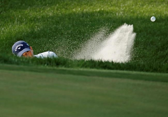 Kevin Kisner hits out of a bunker on the 15th green during the first round of the PGA Championship golf tournament at Bellerive Country Club, Thursday, Aug. 9, 2018, in St. Louis. (AP Photo/Charlie Riedel)