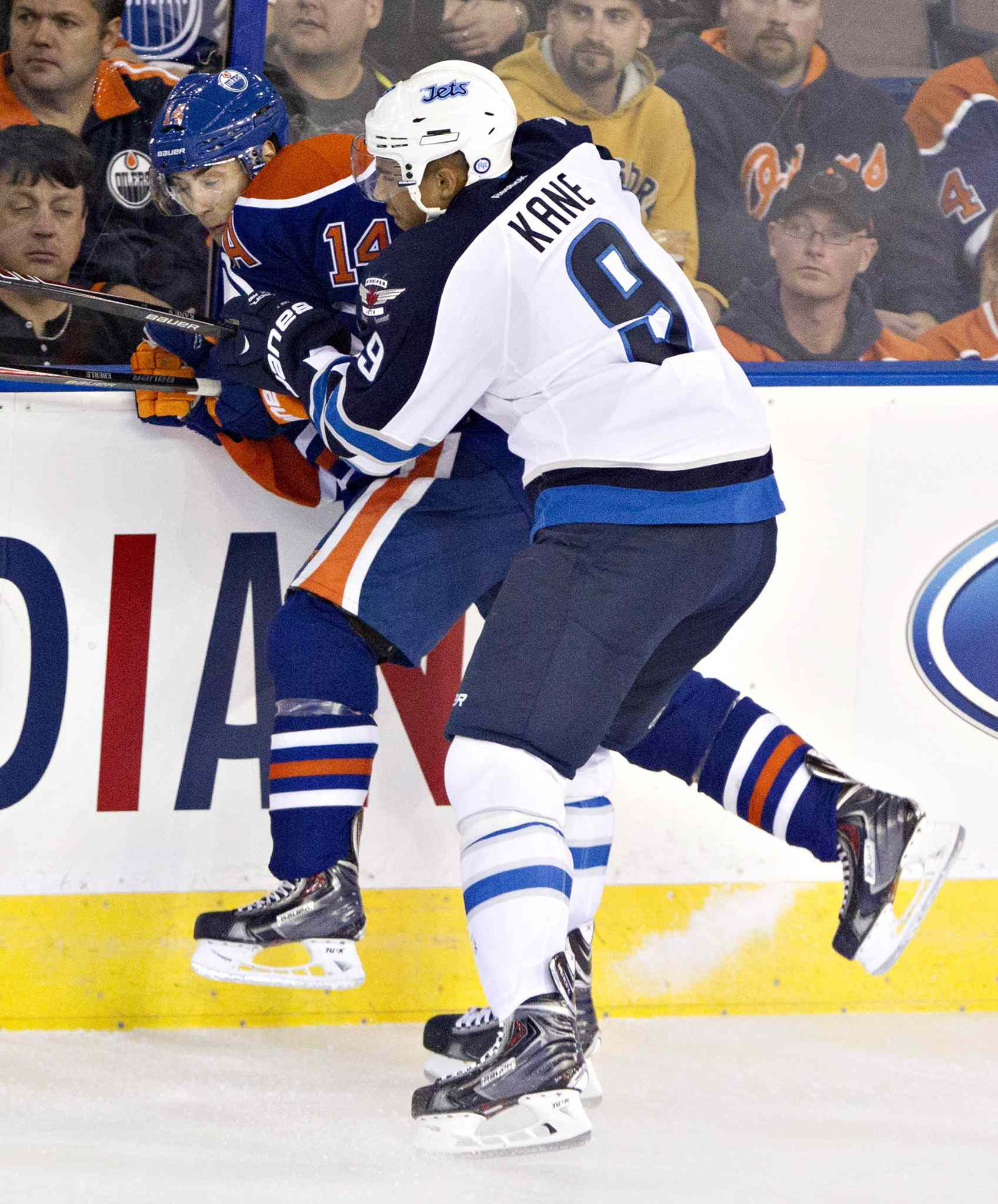 Winnipeg Jets' Evander Kane (9) checks Edmonton Oilers' Jordan Eberle (14) during first-period NHL hockey action in Edmonton Tuesday.