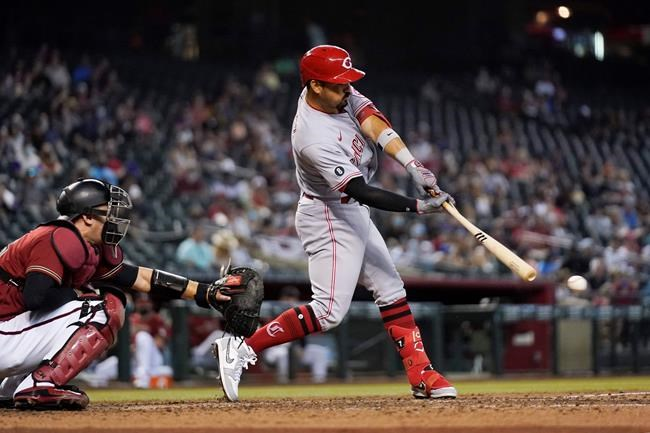 Cincinnati Reds' Eugenio Suarez, right, gets a broken-bat single to break up a no-hit bid by Arizona Diamondbacks starting pitcher Luke Weaver as Diamondbacks catcher Carson Kelly, left, reaches with his glove during the seventh inning of a baseball game Sunday, April 11, 2021, in Phoenix. (AP Photo/Ross D. Franklin)