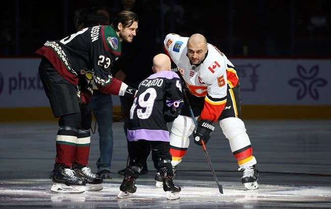 Arizona Coyotes' Oliver Ekman-Larsson (23) drops the puck in front of Leighton Accardo, middle, who is battling cancer, and Calgary Flames' Mark Giordano (5) during an NHL Fights Cancer puck drop ceremony prior to an NHL hockey game, Saturday, Nov. 16, 2019, in Glendale, Ariz. (AP Photo/Ross D. Franklin)