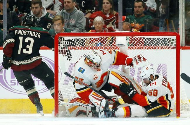 Calgary Flames defenseman Oliver Kylington (58) collides into the net with Flames goaltender David Rittich, middle, after a shot by Arizona Coyotes center Vinnie Hinostroza (13) during the first period of an NHL hockey game, Saturday, Nov. 16, 2019, in Glendale, Ariz. The Coyotes defeated the Flames 3-0. (AP Photo/Ross D. Franklin)