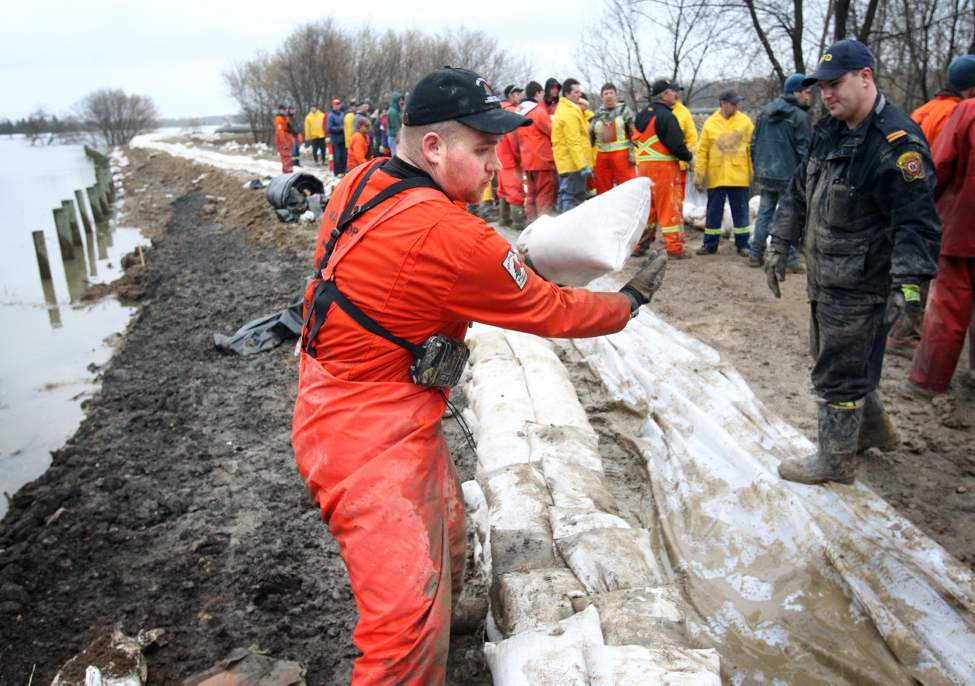 Volunteers, including firefighters and provincial conservation officers, work to fortify the dike set up near Parker Boulevard in the city's north end, Tuesday evening. (Colin Corneau/Brandon Sun)