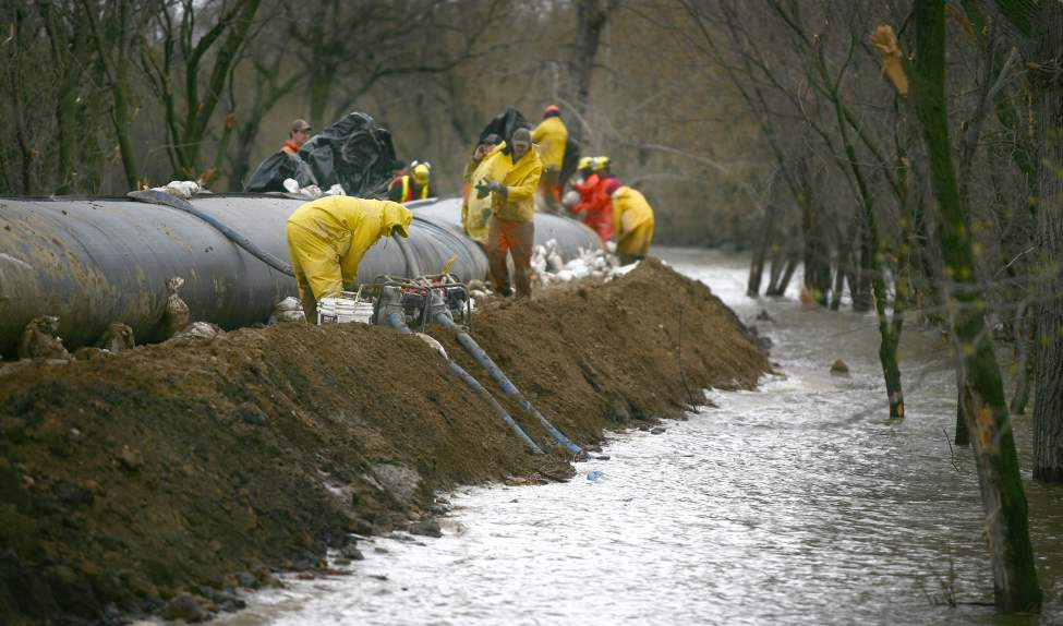 City crews, along with firefighters with Manitoba Conservation, work at topping up the the southern dike with Aqua Dams in preparation of the crest on the Assiniboine River on Tuesday. (Bruce Bumstead/Brandon Sun)