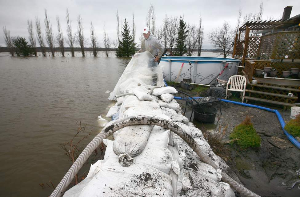 Conrad Winters wraps a sheet of plastic over the top of a sandbag ring-dike protecting his uncle's home along Grand Valley Road on Tuesday morning. (Bruce Bumstead/Brandon Sun)