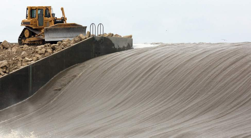 Heavy equipment shore up the walls of the Portage Diversion Tuesday. The diversion is full to capacity running towards Lake Manitoba. May 10, 2011 (JOE BRYKSA/WINNIPEG FREE PRESS)