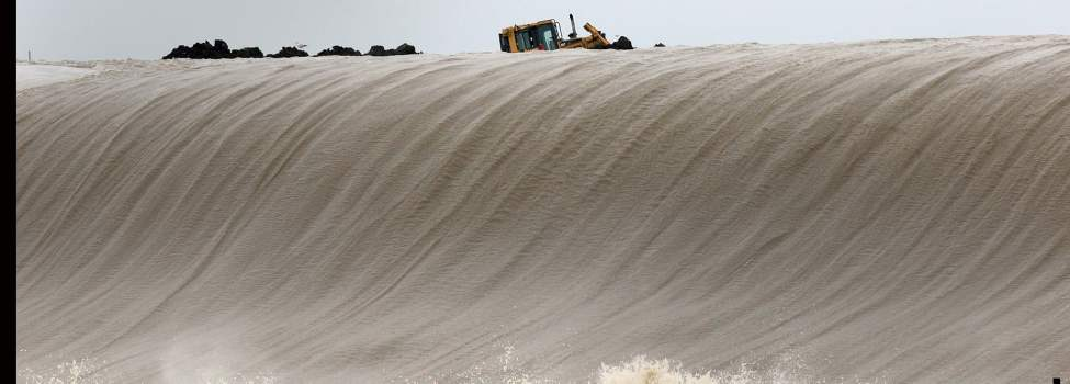 A piece of heavy equipment works to shore up the Portage Diversion Tuesday May 10 at the Drop One location as the at capacity water pours over the drop off. (JOE BRYKSA/WINNIPEG FREE PRESS)