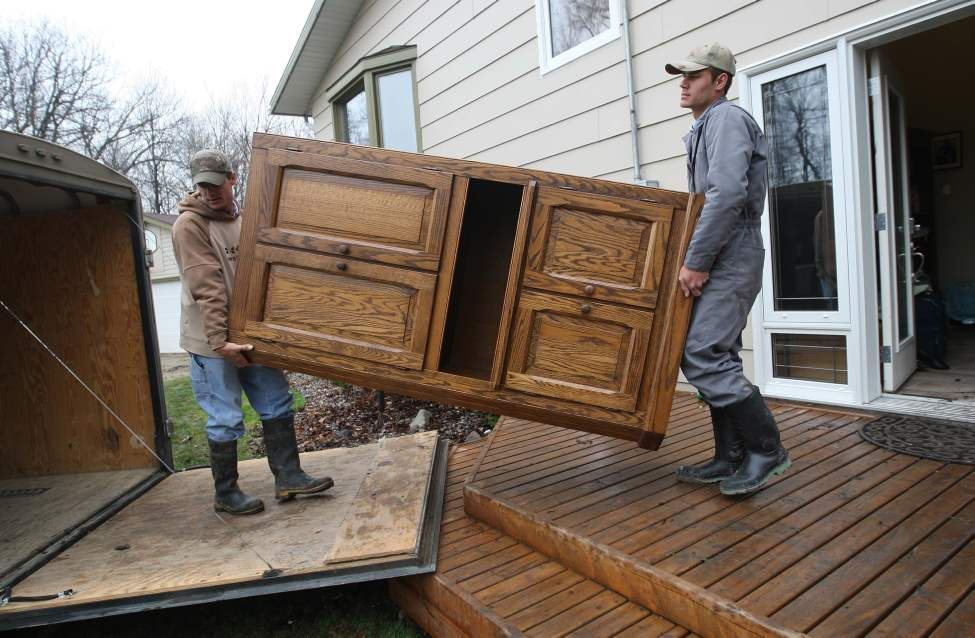 Evacuation underway - Twins Jacob Guenther, left, and David help to move personal items from the Arendse home at Hoop and Holler Bend, Manitoba in preparation of expected flood waters from the proposed cut in the dike. May 10, 2011 (JOE BRYKSA/WINNIPEG FREE PRESS)