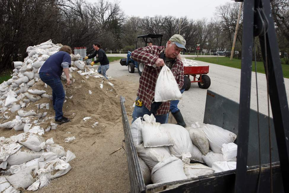 Assiniboine River - Mike Buckmore loads up a trailer with sand bags to protect this property well before a large group of volunteers arrived Tuesday morning in Headingley. (KEN GIGLIOTTI / WINNIPEG FREE PRESS)