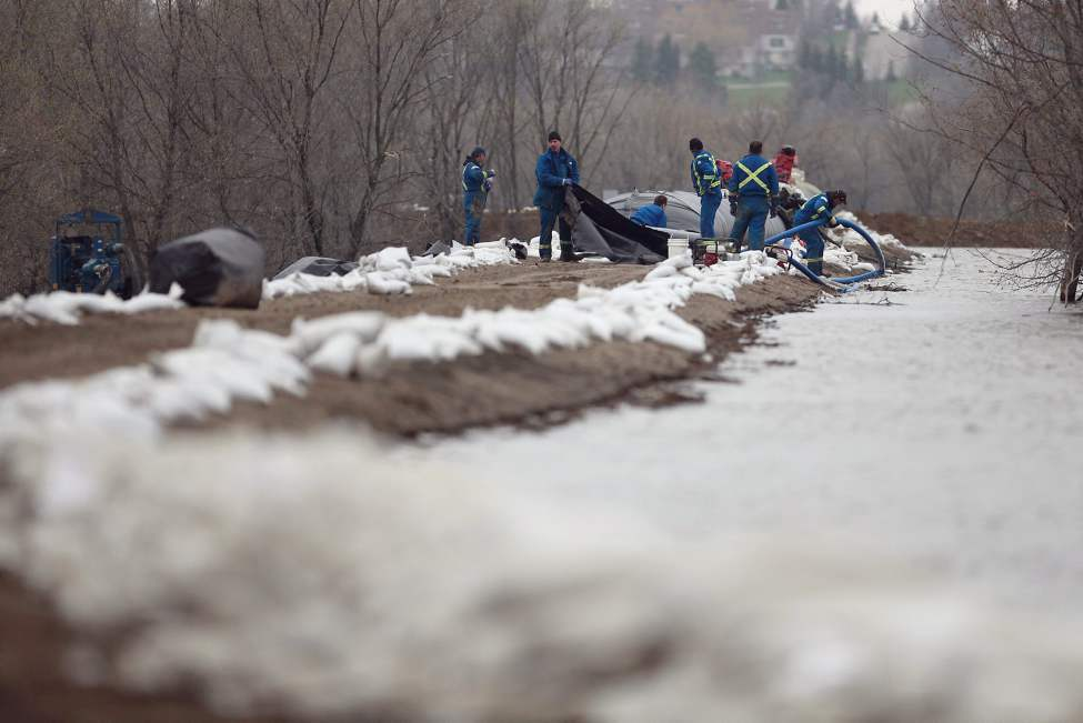 Crews set up an Aqua dam on top of the southern dike of the Assiniboine River in Brandon, Manitoba on Monday, May 9, 2011. The high water levels of the Assiniboine River are threatening surrounding communities.  (THE CANADIAN PRESS/John Woods) (CP)