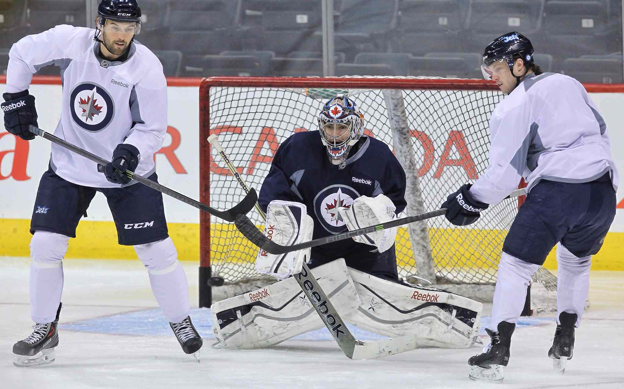 Winnipeg Jets' Eric Tangradi (27) and John Albert (70) try to deflect an incoming puck in front of goaltender Al Montoya (35) during a very short practice Sunday morning at MTS Centre.