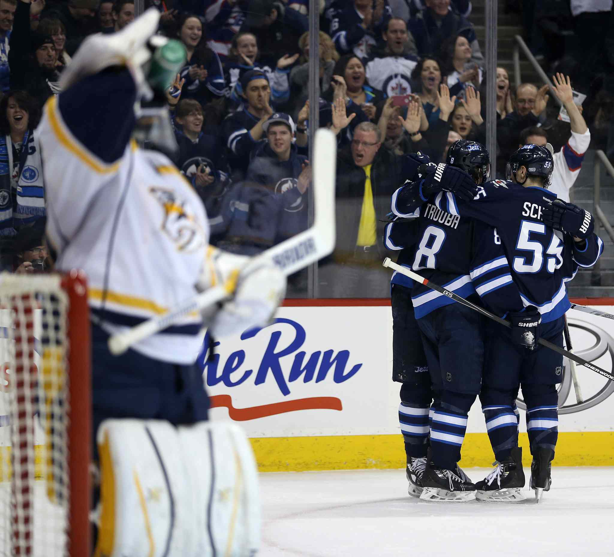Winnipeg Jets players celebrate a goal by teammate Blake Wheeler (26) after he beat Nashville Predators' goaltender Carter Hutton (30) during second period NHL hockey action in Winnipeg.