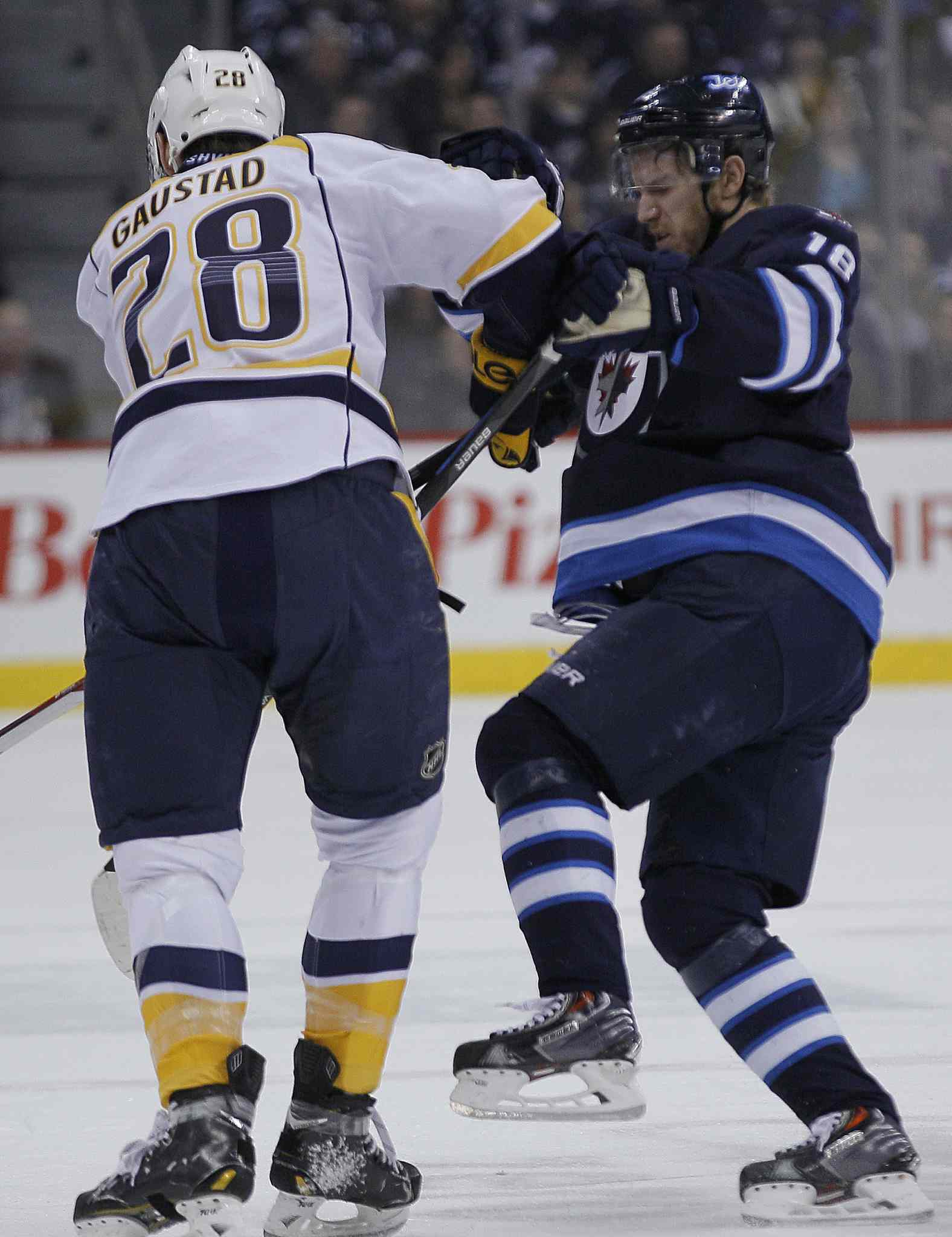 Winnipeg Jets' Bryan Little (18) gets checked by Nashville Predators' Paul Gaustad (28) during second period NHL action in Winnipeg.