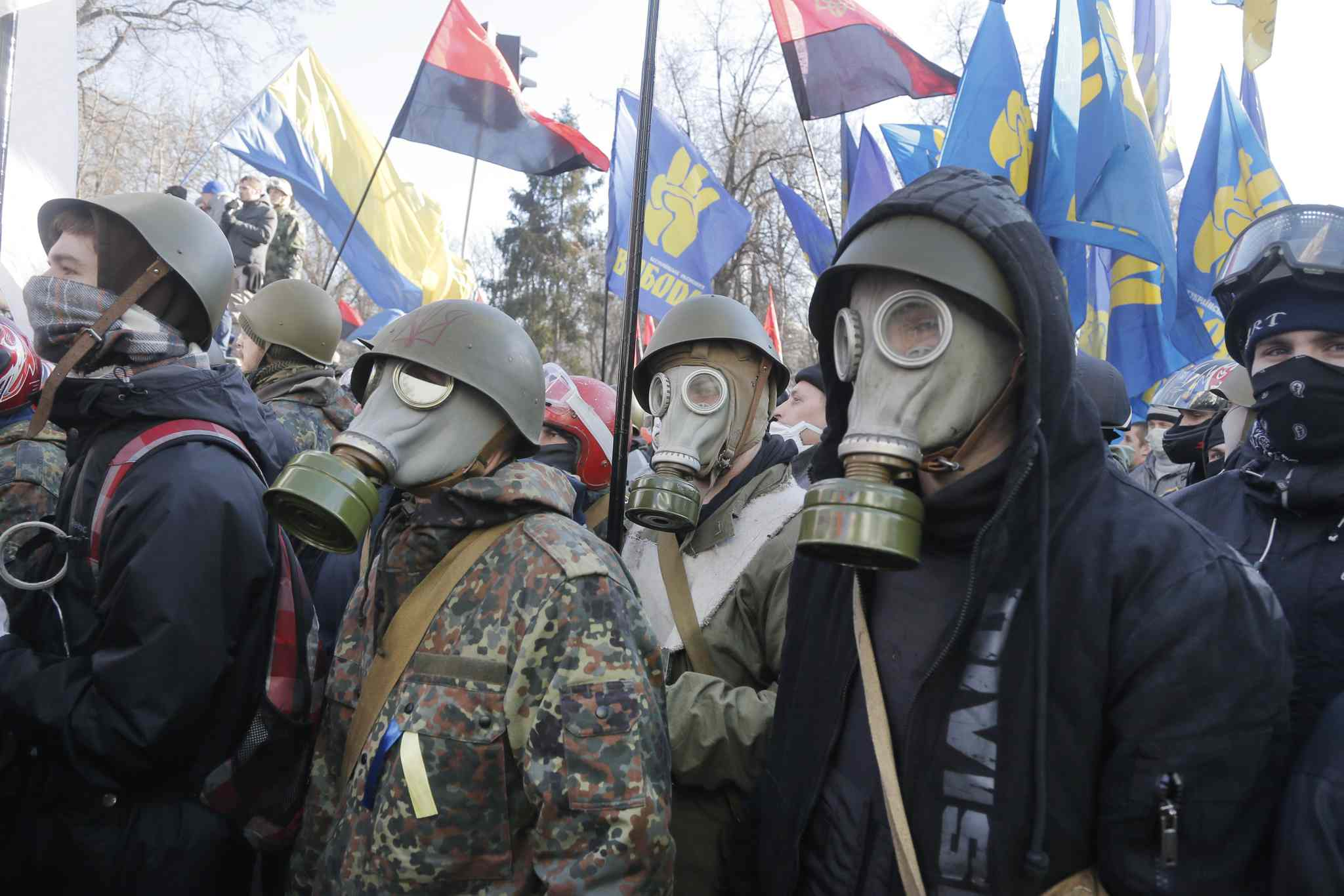 Anti-government protesters look on during clashes with riot police outside Ukraine's parliament in Kyiv on Tuesday.