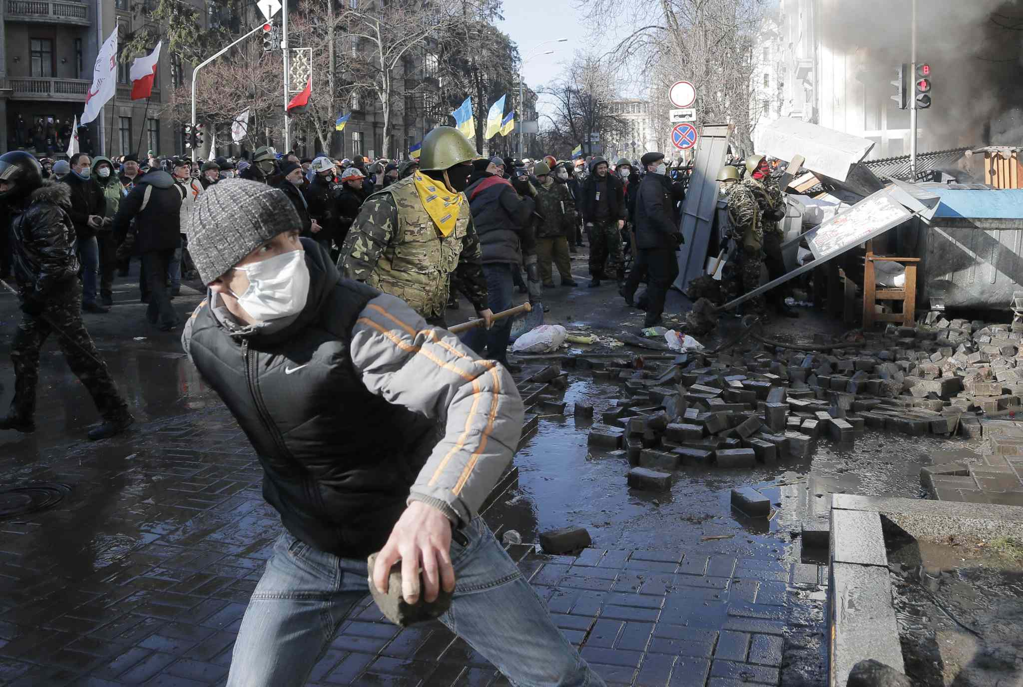 Anti-government protesters lob stones during clashes with riot police outside Ukraine's parliament in Kyiv, Ukraine on Tuesday.