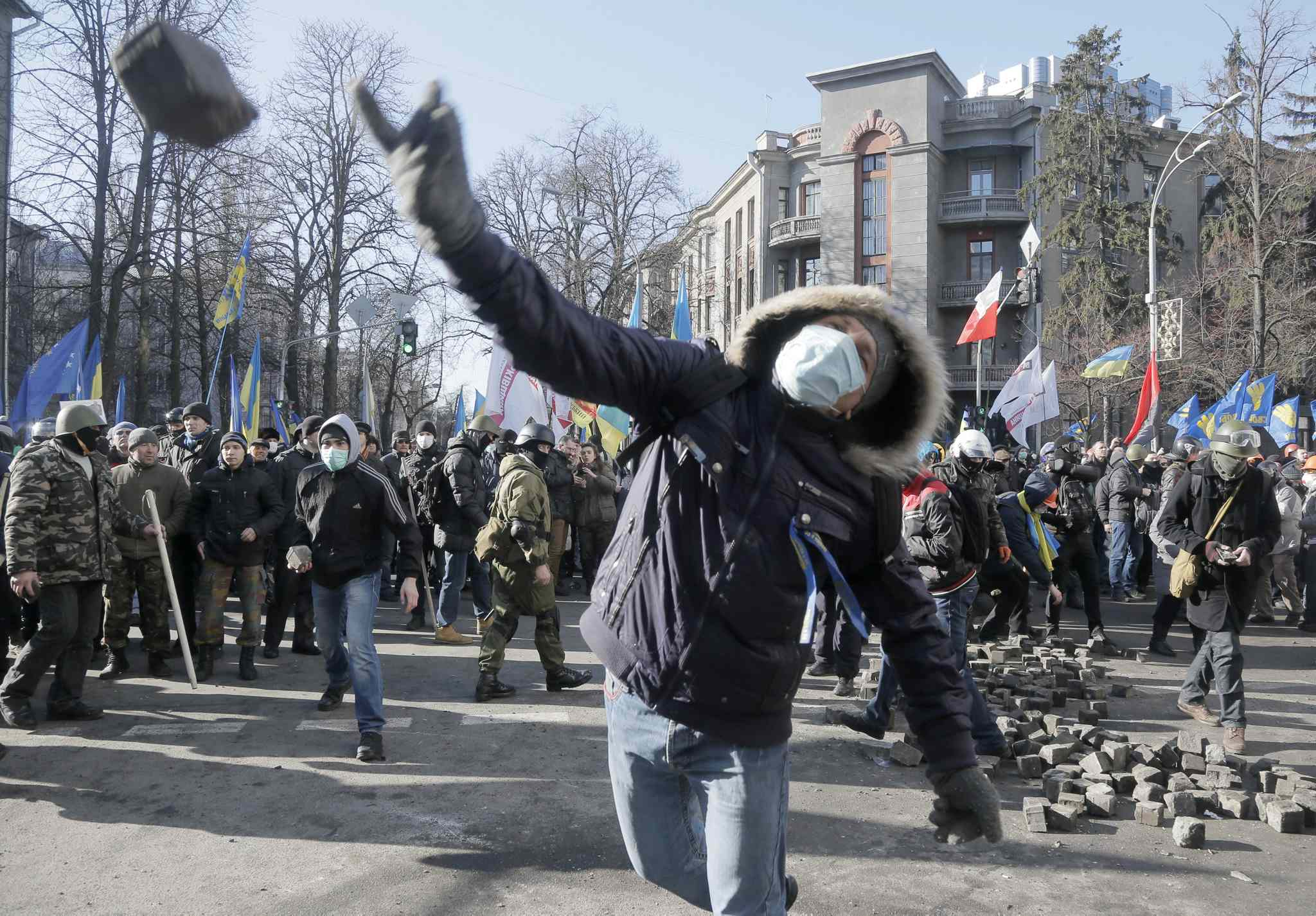 An anti-government protester throws a stone during clashes with riot police outside Ukraine's parliament in Kyiv, Ukraine, on Tuesday. Thousands of angry anti-government protesters clashed with police in a new eruption of violence following new maneuvering by Russia and the European Union to gain influence over this former Soviet republic.