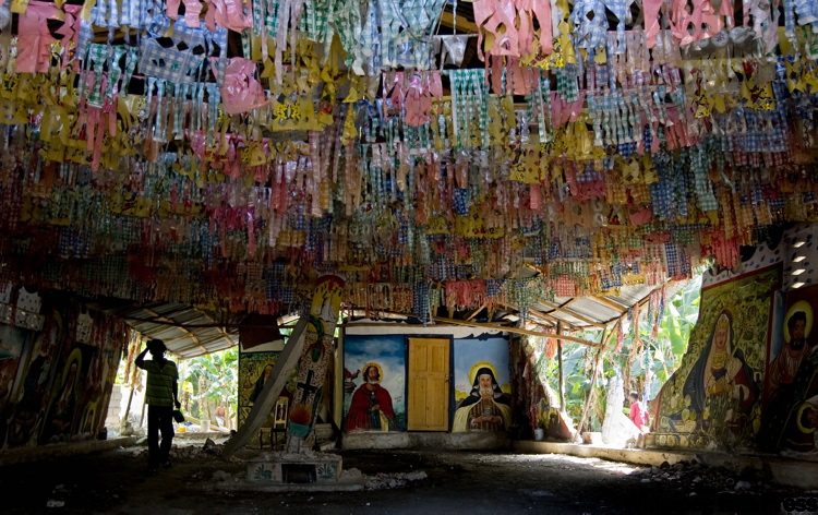A young boy walks in the shadows through a destroyed voodoo church in Leogane, Haiti, earlier this month.