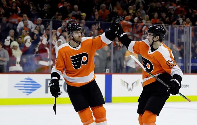 Philadelphia Flyers' Shayne Gostisbehere, right, and Michael Raffl celebrate after a goal by Gostisbehere during the second period of an NHL hockey game against the Detroit Red Wings, Tuesday, Dec. 18, 2018, in Philadelphia. (AP Photo/Matt Slocum)