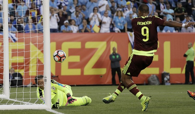 Venezuela's Salomon Rondon right scores a goal past Uruguay's Fernando Muslera during the first half of a Copa America Group C soccer match Thursday