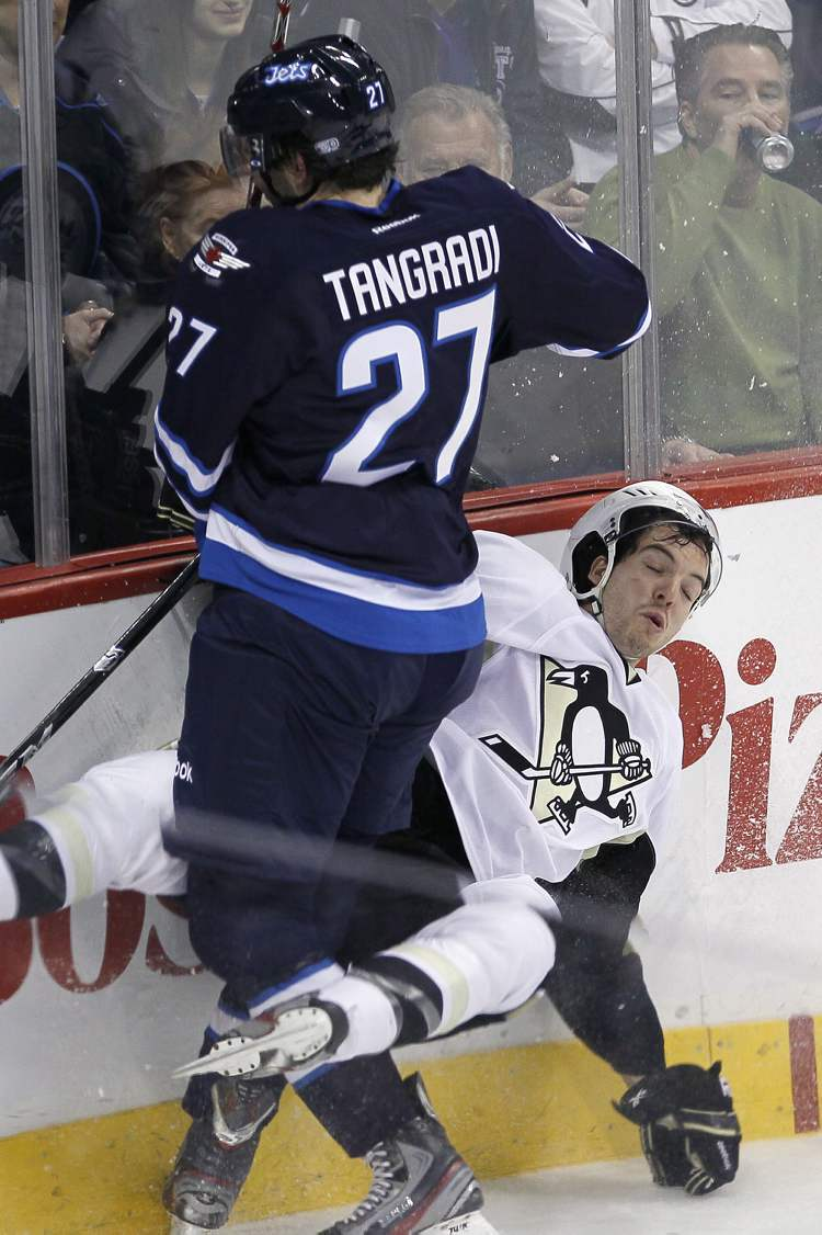 Winnipeg Jets' Eric Tangradi (27) hits Pittsburgh Penguins' Simon Despres (47) during first period NHL action in Winnipeg on Friday, February 15, 2013.  THE CANADIAN PRESS/John Woods