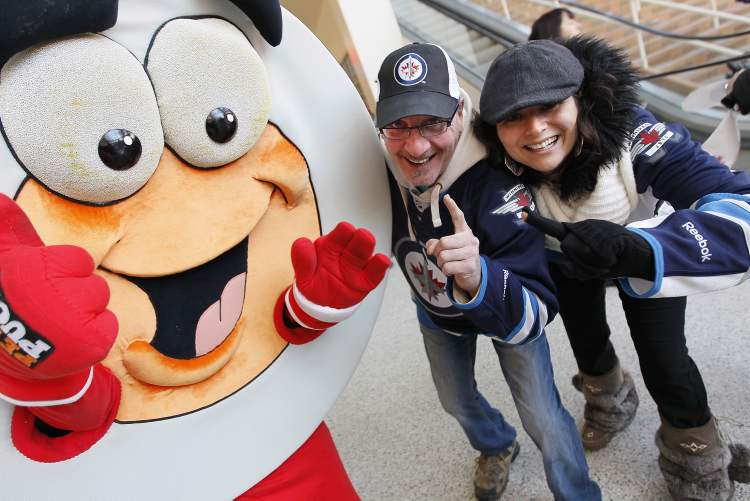 Allen Hurton and Bessie Hatzitrifonos celebrate with Peter Puck prior to NHL action between the Ottawa Senators and Winnipeg Jets in Winnipeg
