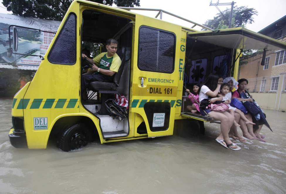 Residents ride along a flooded area in Quezon City, north of Manila, Philippines, on Tuesday Aug. 7, 2012. Relentless rains submerged half of the sprawling Philippine capital, triggered a landslide that killed eight people and sent emergency crews scrambling Tuesday to rescue and evacuate tens of thousands of residents.  AP Photo / John Javellana