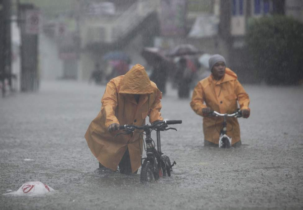 Two men push their bikes along a flooded area in Rizal, east of Manila, Philippines on Tuesday Aug. 7, 2012. Torrential rains pounding the Philippine capital on Tuesday paralyzed traffic as waist-deep floods triggered evacuations of tens of thousands of residents and the government suspended work in offices and schools. AP Photo / John Javellana