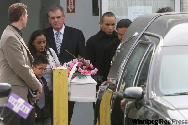 Kim Edwards (left), Phoenix' former foster mom and Edwards' son Andrew Edwards (right) accompany the casket after the service.