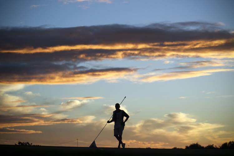 A caddie stands with the flag of the 9th hole during the first round of the Portugal Masters golf tournament at the Victoria golf course in Vilamoura, southern Portugal, Thursday, Oct. 11, 2012. (AP Photo/Francisco Seco)