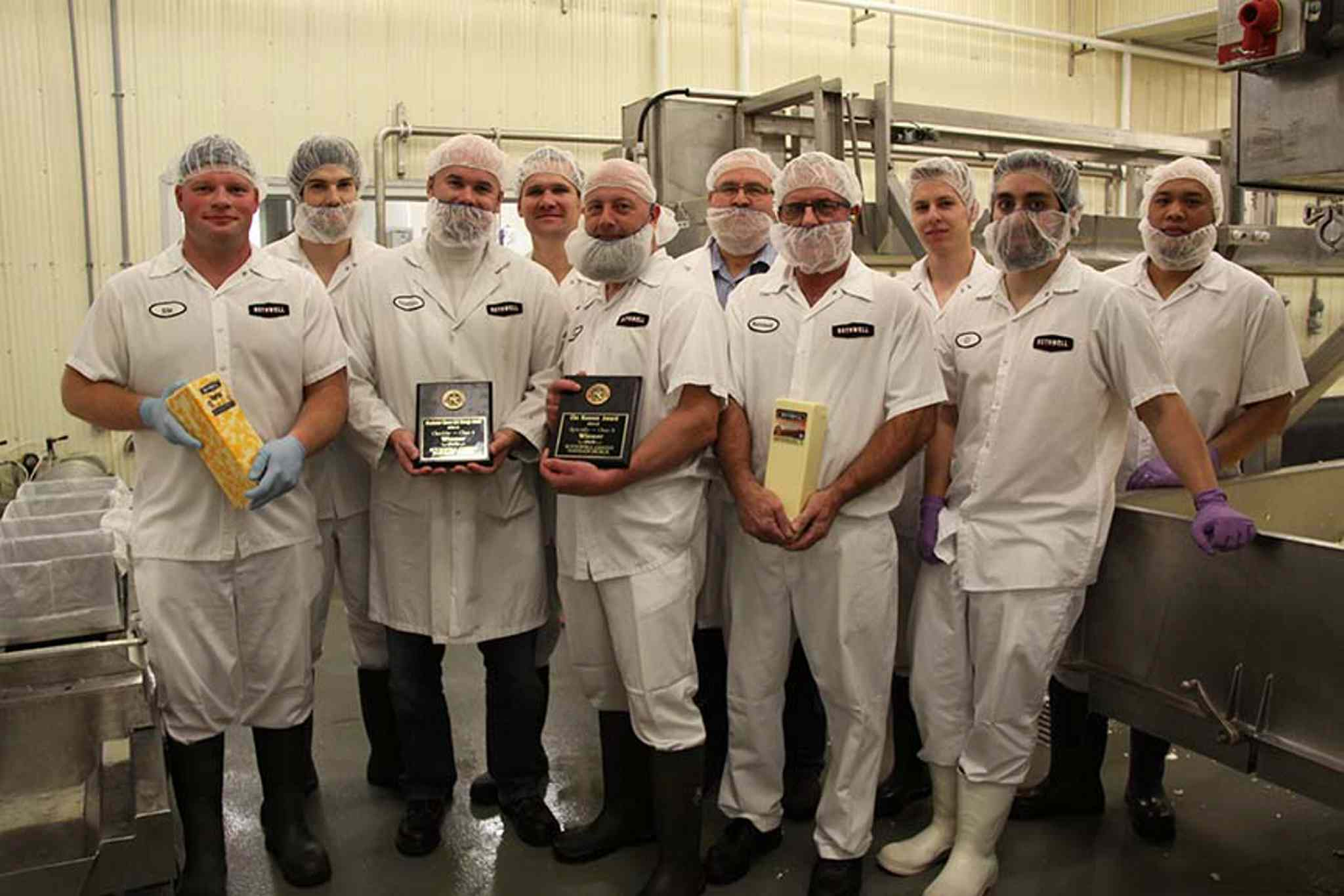 Employees hold Bothwell Cheese awards and products. Front row (from left): Stuart Penner, Nathan Dueck, Gil Dueck, Reinhold Sawatzky and Matthew Tucker. Back row: Matthew Georgeson, Levi Falk, Rob Hiebert, Alex Wiese and Danny Cajurao.