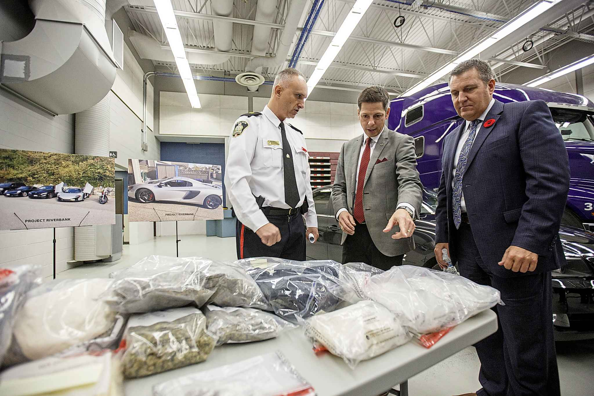 Winnipeg police Inspector Max Waddell shows Winnipeg Mayor Brian Bowman and Cliff Cullen Minister of Justice and Attorney General some of the seized items Thursday.
