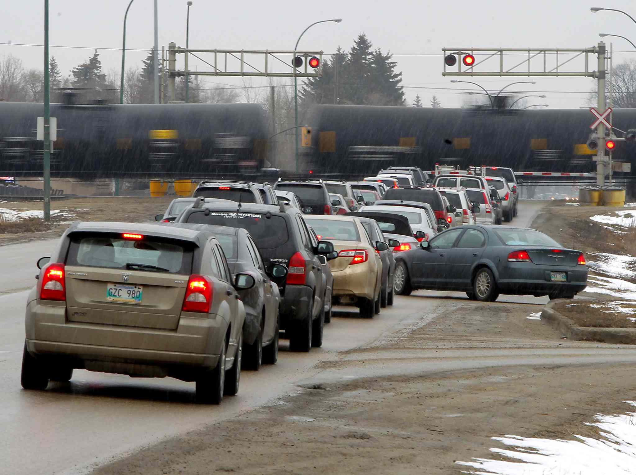 Cars lined up at a rail crossing near Waverley St. in Winnipeg.