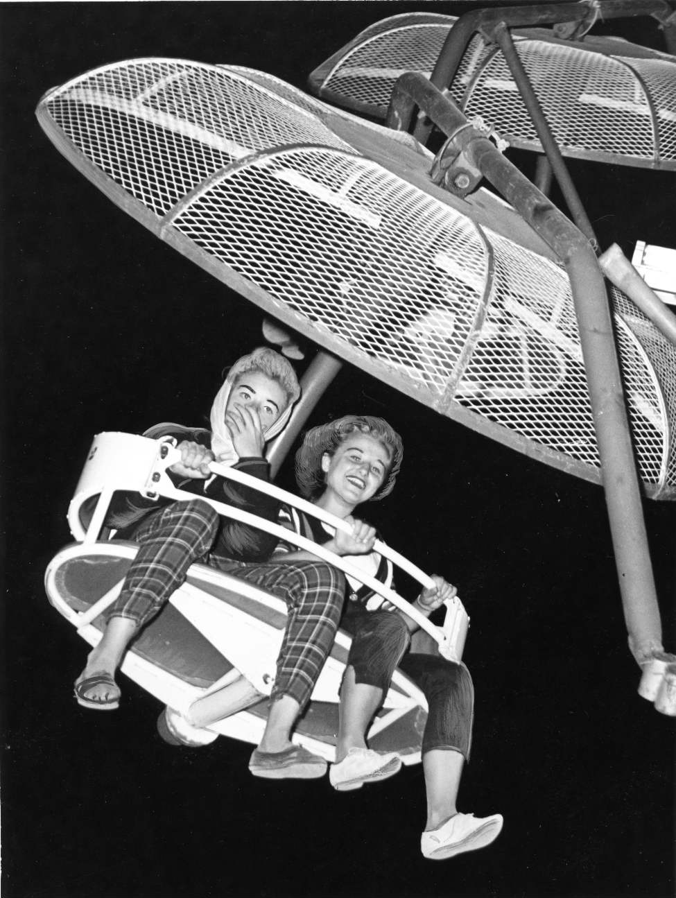 These two girls seem to have mixed opinions about the new Paratrooper ride on the midway at the Red River Exhibition, June 27, 1960.